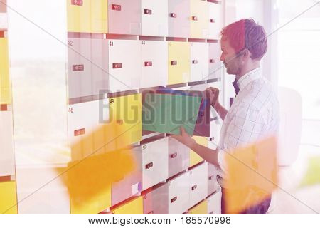 Side view of businessman putting files in locker at creative office