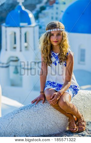 Young girl posing in Old Town of Oia on the island Santorini, white houses, windmills and church with blue domes, Greece