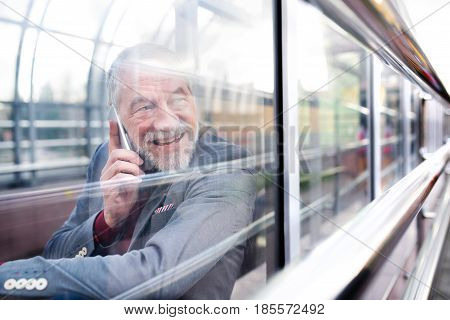 Handsome senior man in gray jacket holding smart phone making phone call. View through glass.