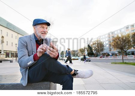 Handsome senior man in town sitting on bench, holding smart phone, texting. Sunny spring day.