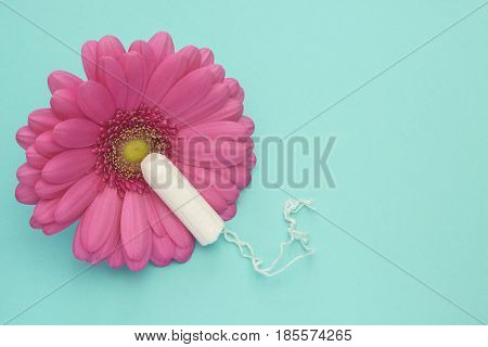 Menstruation tampon and pink gerbera daisy flower. Woman hygiene conception photo. Soft tender protection for woman critical days gynecological menstruation cycle