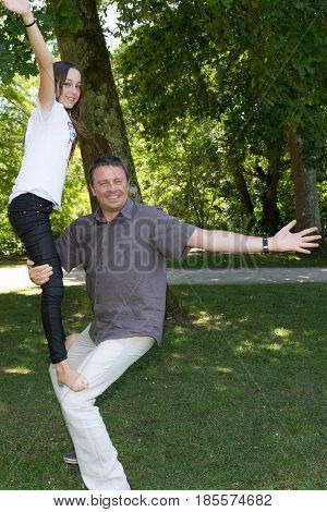 father and his teenager daughter make acrobatics in the park
