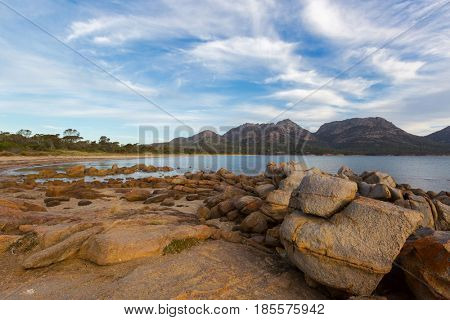 Rocky coastline on Freycinet national park beach in the evening. Big granite rocks during sunset with view of Hazards mountain range from Coles Bay. East coast of Tasmania, Australia