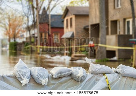 Close shot of flood Protection Sandbags with flooded homes in the background