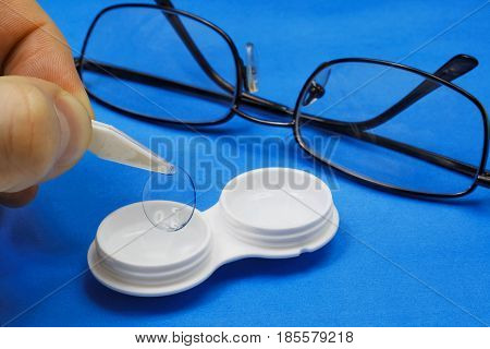 Removing the soft contact lens from the storage case. In the background ordinary glasses