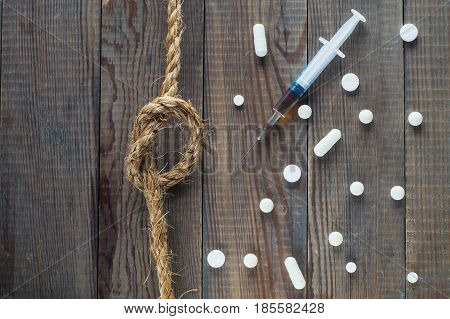 Concept Stop drugs: a syringe pills and a rope with a knot on a wooden background. No drugs or anti doping in sport or zero tolerance to drugs. Drugs pills top view flat lay.