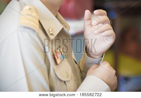 Thai teacher buttoning on the sleeve in formal officer government uniform with Brown suite and Golden stripe on shoulder thailand educatio