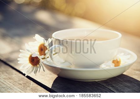 White porcelain cup and a bouquet of camomiles on a wooden table.