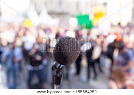 Protest. Public demonstration. Political rally. Microphone in focus, against blurred crowd.