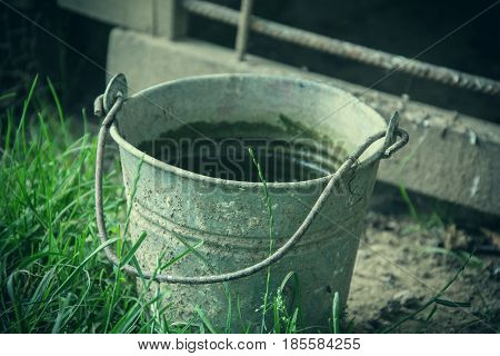 Close up of rusty iron bucket in grass in the garden. Dirty gray metallic bucket with garbage on barnyard at sunny day. Gardening background. Containers for storing feed trash water paint