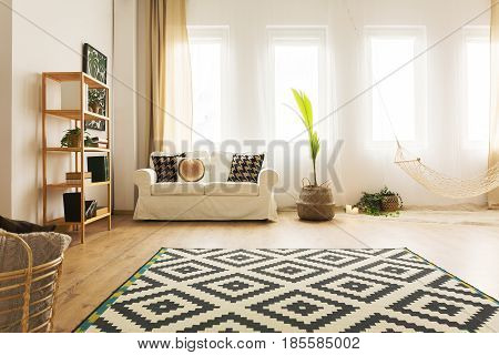 Modern warm home interior with hammock sofa carpet and bookcase