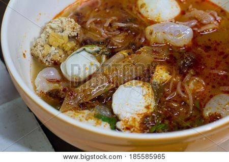 Tom Yum Kung with noodles and seafood popular Thai food. Tom Yum Goong Spicy Sour Soup on wooden table top view Thai local food