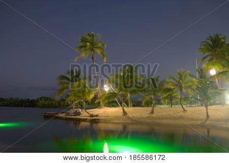 Man made sandy beach by night illuminate by lanterns at Camana Bay, Grand Cayman