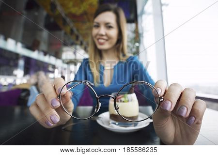 Pretty young girl holding glasses in hands sitting in cafe, ophthalmology, close up