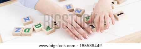 Close-up of teacher's and girl's hand placing the letters