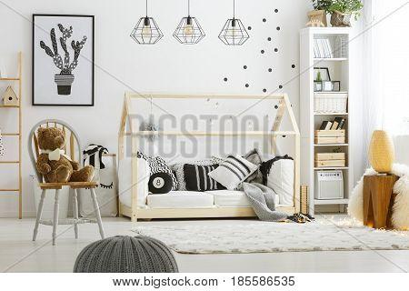Black decoration in cozy white room designed in scandi style