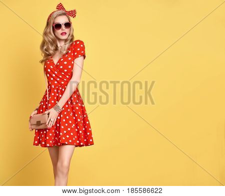 Fashion PinUp Model Girl in Red Polka Dots Summer Dress. Stylish Curly hairstyle, Trendy Clutch, fashion Headband, Sunglasses. Beauty Blond Woman in fashion pose. Glamour Playful Sexy Lady on Yellow