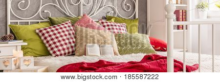 Open book on the comfortable white bed with colorful pillows