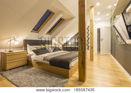 Spacious bedroom with king-size bed wooden accessories and tv
