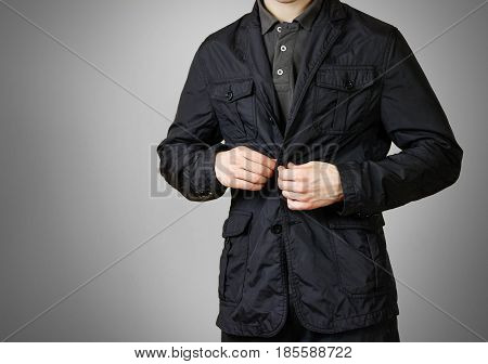 A Man In A Black Jacket. Buttons Of The Hand Button. Isolated On Grey Background