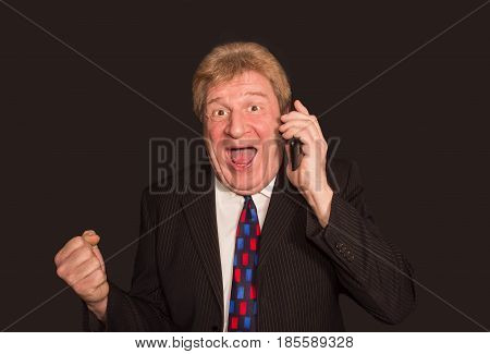 Good news. Surprised senior man in formalwear holding mobile phone and standing against black studio background