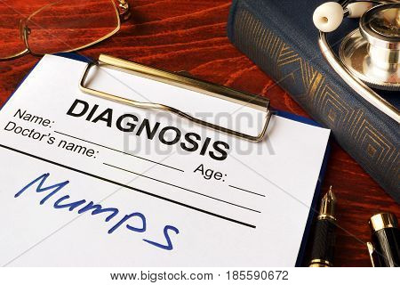 Medical form with diagnosis Mumps on a table.