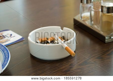 ashtray and cigaretteon a table ash tray glass addiction b