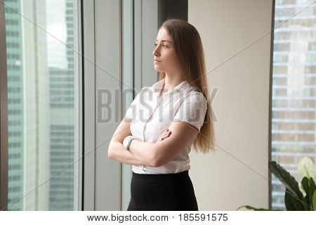 Beautiful woman in formal wear standing with arms crossed and looking in window. Successful businesswoman looking into future with confidence. Ambitious female entrepreneur thinking about perspectives