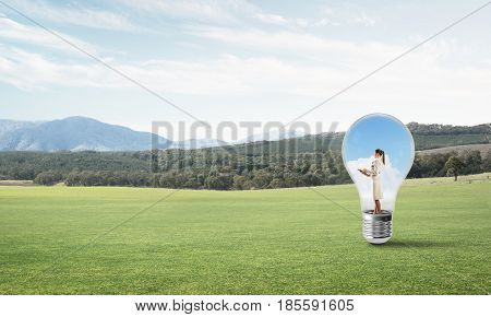 Young businesswoman trapped inside of light bulb on green grass