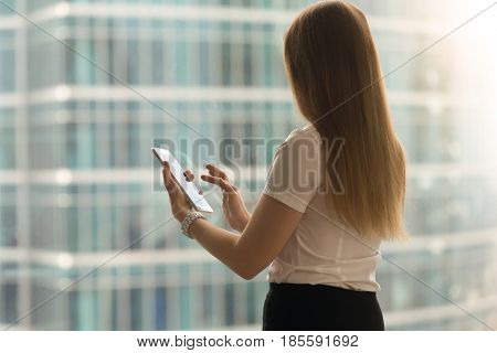 Standing woman back view swipe with finger on tablet screen. Businesswoman using modern touchscreen compact computer for business tasks in office. Female entrepreneur reading news with phablet