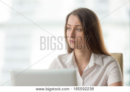 Lost in thoughts businesswoman thinking of solution. Worried female sitting alone in office looking away. Female entrepreneur ponders decision at workplace. Absent minded young woman tired, distracted
