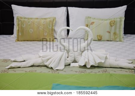 Pillow and blown pillow and fold the towel as a swan kiss each other on the white bed in bedroom