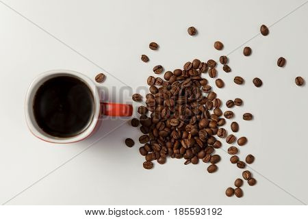 Cup Of Hot Coffee And Beans Coffee On White Table