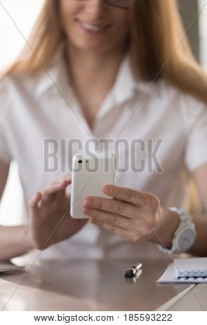 Smiling woman sitting at desk and touching cellphone screen. Businesswoman reading message, or browsing online on phone. Mobile entertainments, sharing news or photos in social networks. Close up photo