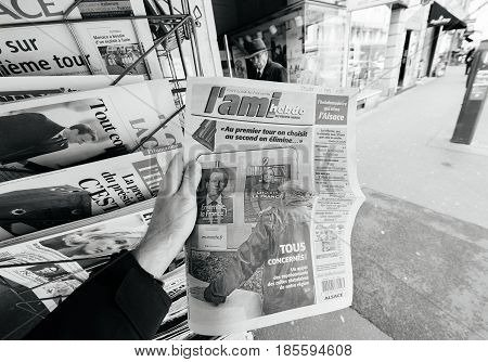 PARIS FRANCE - MAY 9 2017: Pov buying L'Ami Hebdo newspaper front page picture of the newly elected French president Emmanuel Macron second round French Presidential election