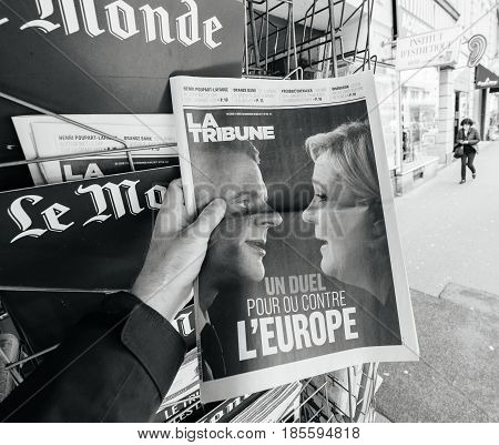 PARIS FRANCE - MAY 9 2017: Pov buying La Tribune newspaper front page with the picture of the newly elected French president Emmanuel Macron and Le Pen after the second round French Presidential election
