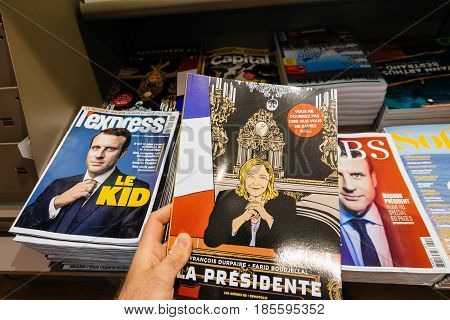 PARIS FRANCE - MAY 9 2017: Pov buying La Presidente Marine Le Pen comics with surrounded magazines with faces of Emmanuel Macron - the newly elected French President