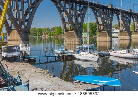 Dnipro Ukraine - April 30 2017: Participants of the local yacht-club anchorage near an arched bridge working with lifting sailboats to water at spring season
