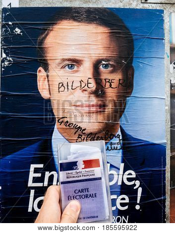 PARIS FRANCE - MAY 9 2017: Emmanuel Macron portrait poster detail next to polling place after the second round of the French presidential election with the marker inscription Member of Bilderberg group