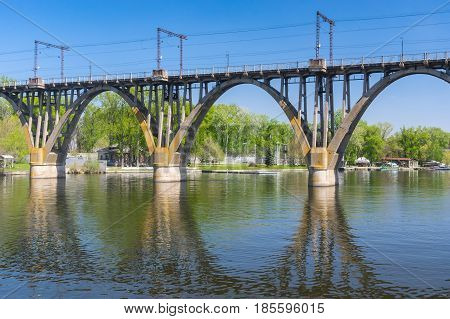 Spring landscape with classic arched bridge and it's reflection on the Dnipro river the water in the Dnipro city Ukraine.