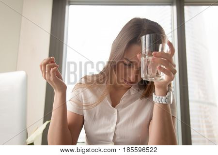 Businesswoman suffering from head ache at workplace. Stressed young woman puts glass of water to forehead and holding pill in hand. Female feeling sudden sickness at work. Addiction after medicines