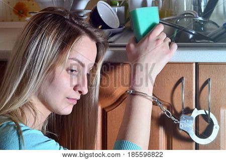 Sad And Tired Girl Handcuffed To A Kitchen Counter With A Lot Of Unwashed Dishes