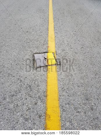 Sewer hatch with metal frame on urban road,Yellow road line over the metal sewer hatch.