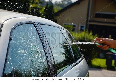 Young Men Washing Silver Car With Pressured Water And Brush At Sunny Day. Close Up Of Cleaning Car O