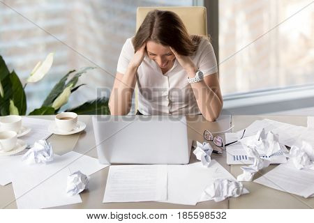 Desperate busy businesswoman sitting at desk covered crumpled paper. Woman in panic, fails in business, too much overwork. Female entrepreneur goes mad because of missing deadline. Lack of ideas
