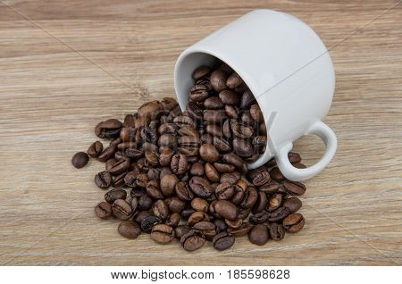 Overturned Cup And Scattered Roasted Coffee Beans On Table