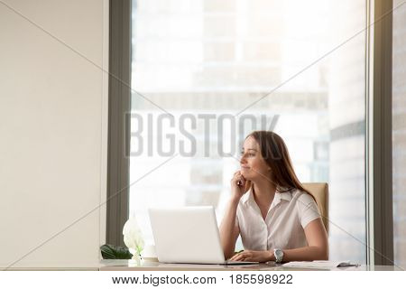 Satisfied businesswoman dreams about success at workplace. Pensive young woman imagines great achievement in business. Female entrepreneur visualizes in imagination desired positive result. Copy space