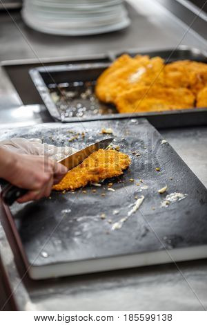 Chef cut breaded german weiner schnitzel in restaurant kitchen