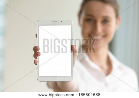 Close up image of digital tablet in hand of smiling woman on background. Female showing blank mock up phablet screen with copy space. Presenting new electronic gadget model. Mobile apps, services ad