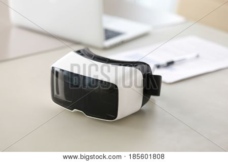 Virtual reality glasses on table, documents and laptop on background. Futuristic business instrument for augmented reality, 3d visualization. Modern VR technology in business, virtual office concept